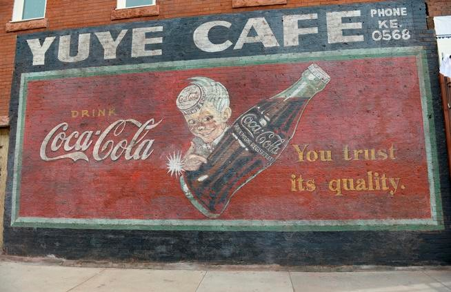 As crews removed stucco covering the exterior of a building, they found this Coca-Cola ad, which they worked to preserve. (Kathryn Scott Osler, The Denver Post)
